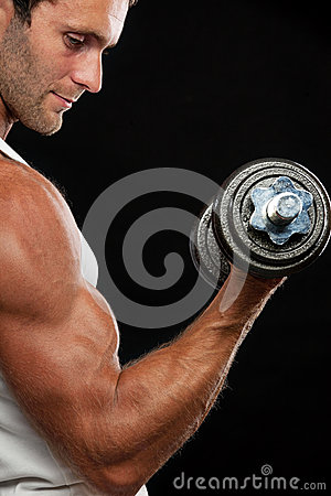 Muscular man lifting dumbbell