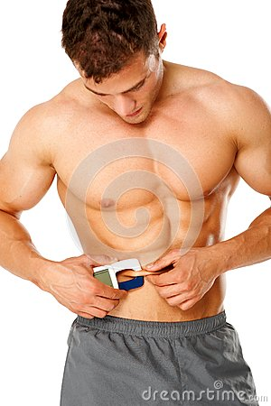 Muscular man measures level of fat on his body