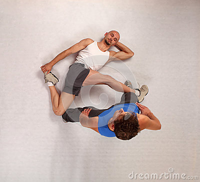 Muscular man stretching with personal trainer
