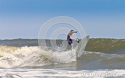 Muscular man surfing