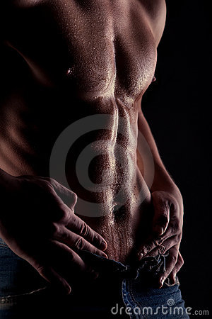 Muscular naked man with water drops on stomach