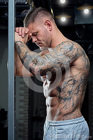 Free Muscular Shirtless Shredded Strong Tired Man With Blue Eyes And Tattoo Poses On A Power Cage In A Gray Pants In A Gym Royalty Free Stock Photography - 111709837