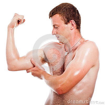 Muscular sports man checking biceps