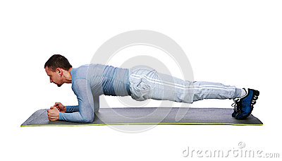 Muscular sportsman practicing yoga on a mat