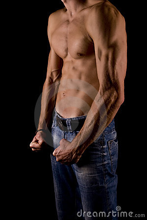 Muscular young male body on black background.