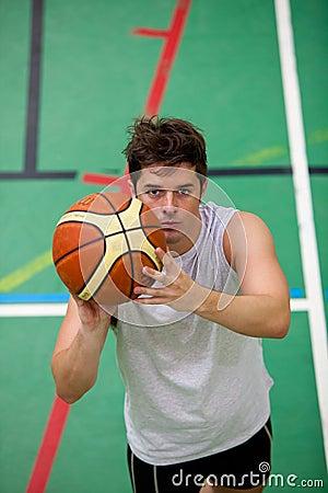 Muscular young man playing basket-ball