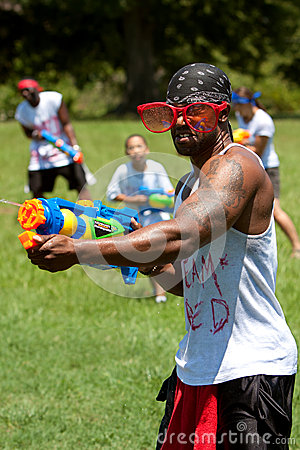 Muscular Young Man Squirts People With Water Gun Editorial Stock Image