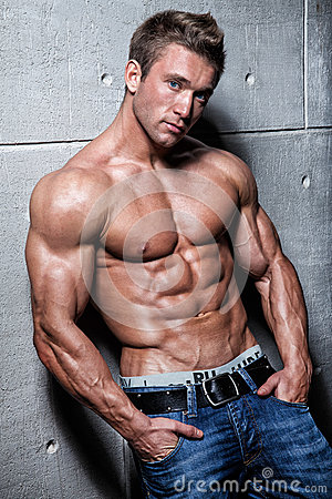Muscular young sexy guy posing in jeans and bare-chested