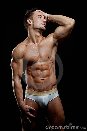 Muscular young sexy wet naked guy posing in trunks