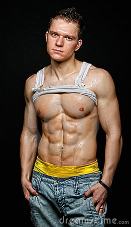 Muscular young wet sexy man in the white t-shirt