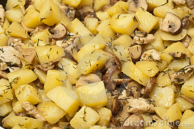 Mushrooms and potatoes frying in a pan