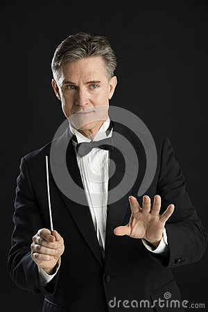 Music Conductor Gesturing While Directing With His Baton