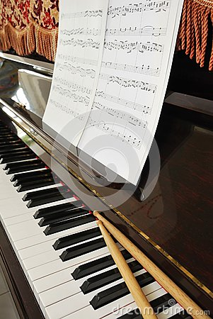 Music score and drum sticks on piano keyboard