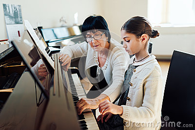 Music teacher shows how to play piano Stock Photo