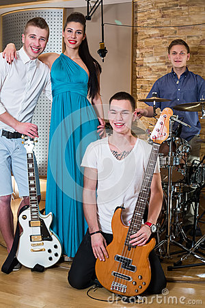 Musical group of three guys and one girl in Recording Studio
