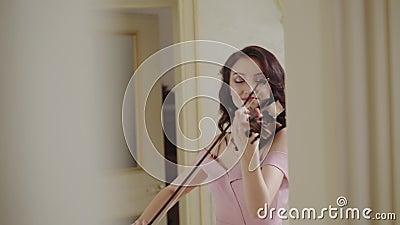 Musical rzemiosło exultant żeńską skrzypaczką przy kamerą w lekkim pokoju, emocjonalnie zbiory