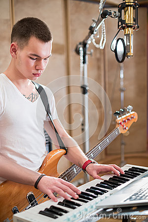 Musician with a guitar around his neck plays keyboard