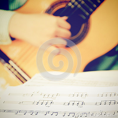 Musician playing classical guitar with musical chords