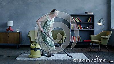 Musique de écoute de femme agée heureuse sur des écouteurs et danse avec un aspirateur, amusement à la maison banque de vidéos