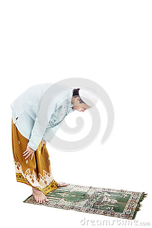 Muslim man bowing on prayer mat