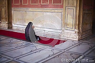 Muslim woman in sari kneeling and praying at the m Editorial Stock Photo
