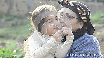 Muslimsk farmor kysser sin lilla flicka barnbarn i trädgård tillsammans lager videofilmer