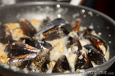 Mussels being fried in pan