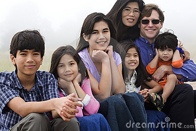 Mutiracial family sitting on beach