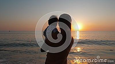 Mutter hält sich in den Armen, während sie sich den Sonnenuntergang am Meer oder am Meeresufer ansieht stock video footage
