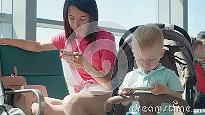 Mutter mit zwei Kindern, unter Verwendung der Geräte, zum auf von Abfahrt im Warteraum zu warten am Flughafen stock video