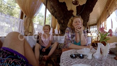 Mutter Und Kleine Tochter Sitzen Im Café Mutter Spricht Und Mädchen Lacht Und Neckt Ihr Vater ` S Bein Stock Footage - Video von haltung, mädchen: 89293326