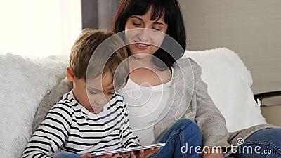 Mutter und Sohn verbringen Zeit zusammen auf dem Sofa und schauen sich einen Film mit einem Tablett an Gute Familie, Technologie  stock footage