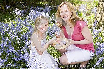 Mutter und Tochter auf Ostern, das nach Eiern sucht