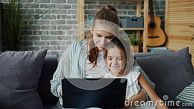 Mutter und Tochter, die Laptops verwenden, die sich den Bildschirm mit Technologie zu Hause ansehen stock footage