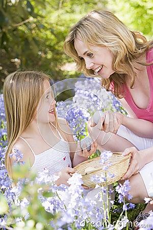 Mutter und Tochter Ostern, das nach Eiern sucht