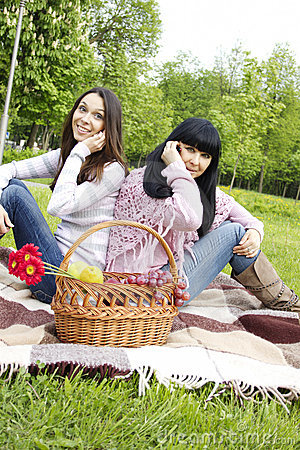 Mutter und Tochter sprechen am Telefon im Park