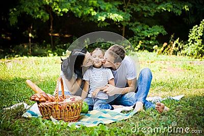 Familie die picknick auf einer parkwiese hat küssen