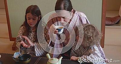Mutter und zwei Kinder trinken Tee und essen bei Ryokan in Japan stock video footage