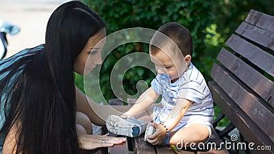 Mutter versucht, die Aufmerksamkeit ihres Sohns zu erregen, der auf der Bank sitzt stock footage