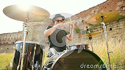 Muzyk perkusista, gra w zestaw bębnowy i cymbały, na ulicy w słonecznej pogodzie zbiory