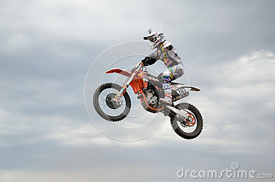 MX racer performs a jump in background of clouds Editorial Image