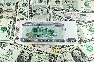 Myanmar kyats on many dollars background