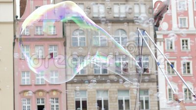 Mydlani bąble festiwale, mężczyzna z bąbel różdżką zabawiają ludzi przy miasta wydarzeniem na tle architektura zbiory