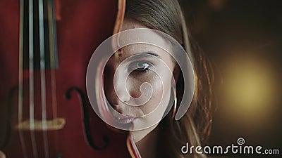 Mysteriöser und leidenschaftlicher Blick auf Kamera des Mädchens mit Violine am Gesicht stock footage