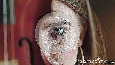 Mysteriöser und leidenschaftlicher Blick auf Kamera des Mädchens mit Violine am Teil des Gesichtes stock footage