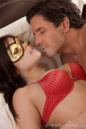 Mysterious woman in fetish mask seducing man