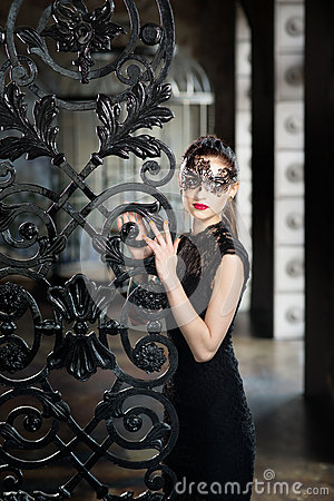 Free Mysterious Woman In Venetian Carnival Mask Near Wrought Iron Gate Stock Images - 84129594
