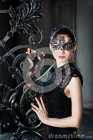 Free Mysterious Woman In Venetian Carnival Mask Near Wrought Iron Gate Royalty Free Stock Photography - 84135017