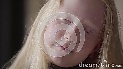 Nära övre stående av en albinoflicka med gråa ögon som ser le för kamera Ovanligt utseende Carefree barndom lager videofilmer