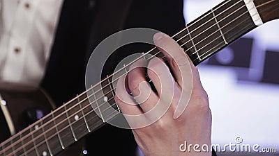 Närbild av fingrar som organiserar om ackord på den akustiska gitarren lager videofilmer